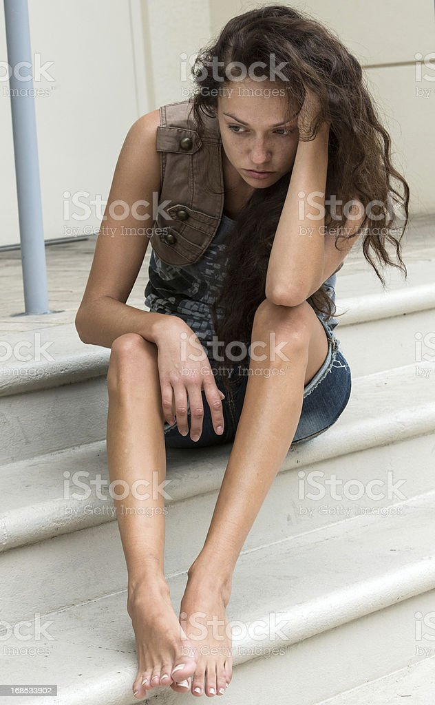 Sad Teenage Girl Sitting on Outdoor Steps stock photo