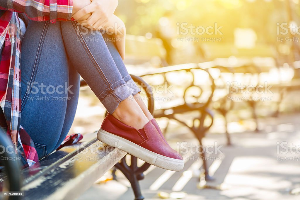 Sad teenage girl sitting on the park bench stock photo
