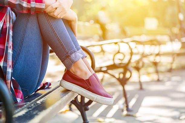 sad teenage girl sitting on the park bench - sitzbank schuhe stock-fotos und bilder