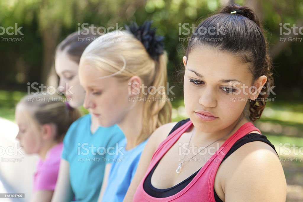 Sad teenage girl with friends at school royalty-free stock photo