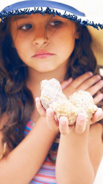 traurige teenager-mädchen mit breitkrempigen hut hält muscheln in der hand. das konzept der sommerferien, ökologie. - meerjungfrau wellen stock-fotos und bilder