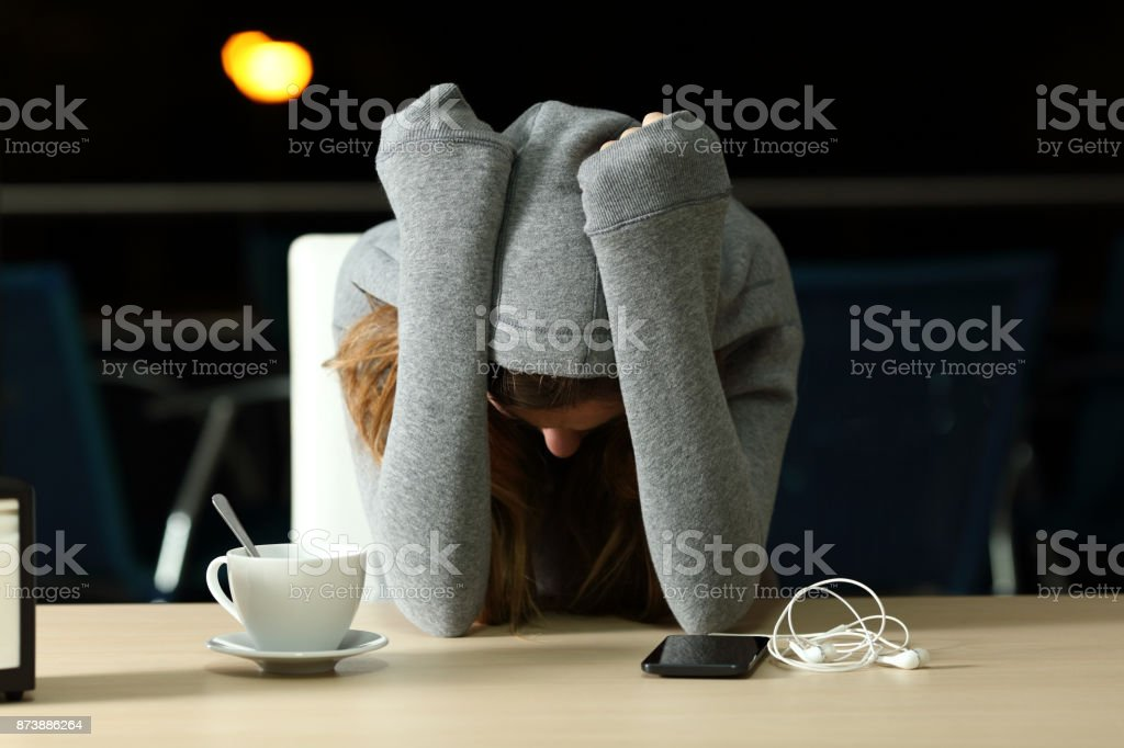 Sad teenager complaining in a bar in the night stock photo