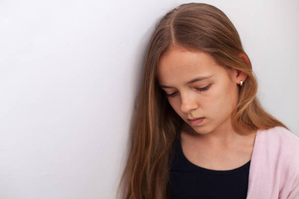 Sad teenager girl standing by the white wall with downcast eyes stock photo