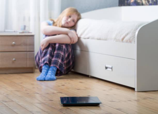 sad teenager girl with scales on floor stock photo