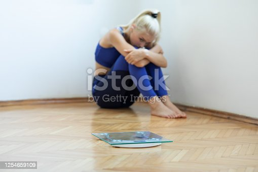 Sad teenager girl with scales on floor
