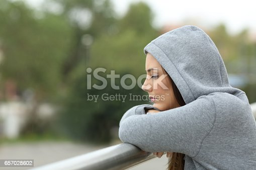 istock Sad teenager looking down in a balcony 657028602