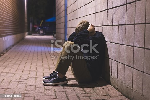 The image displays a sad teen boy sitting in an alleyway all alone at night.