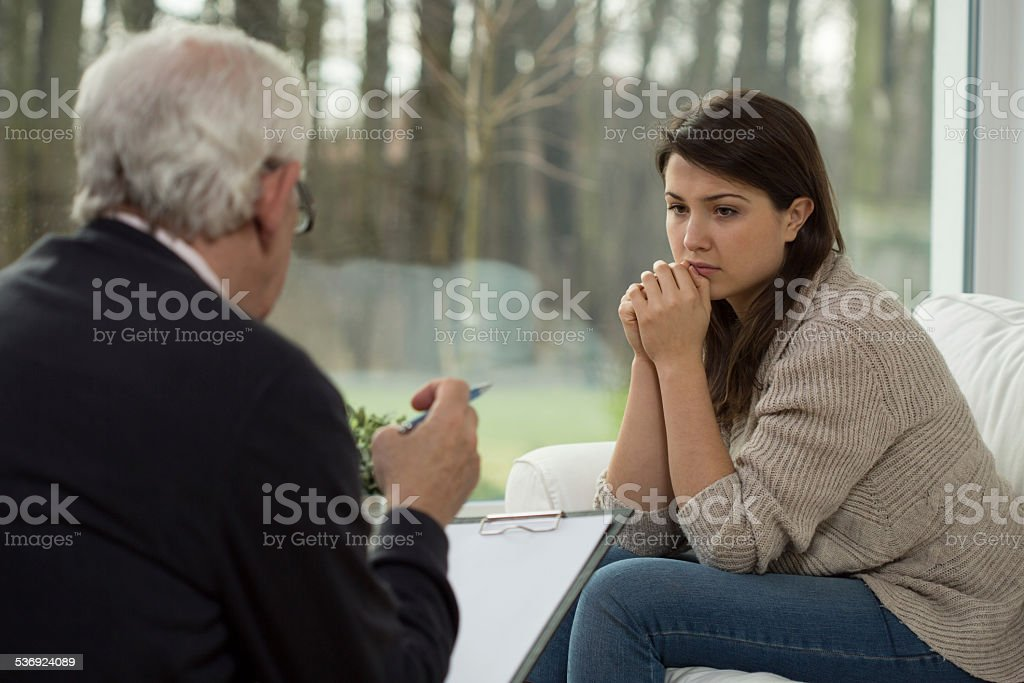Sad teenager talking with psychologist stock photo