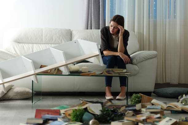 Sad tenant complaining after home robbery in the night stock photo