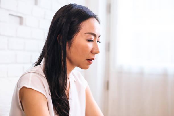 Sad thoughtful Asian female at home stock photo