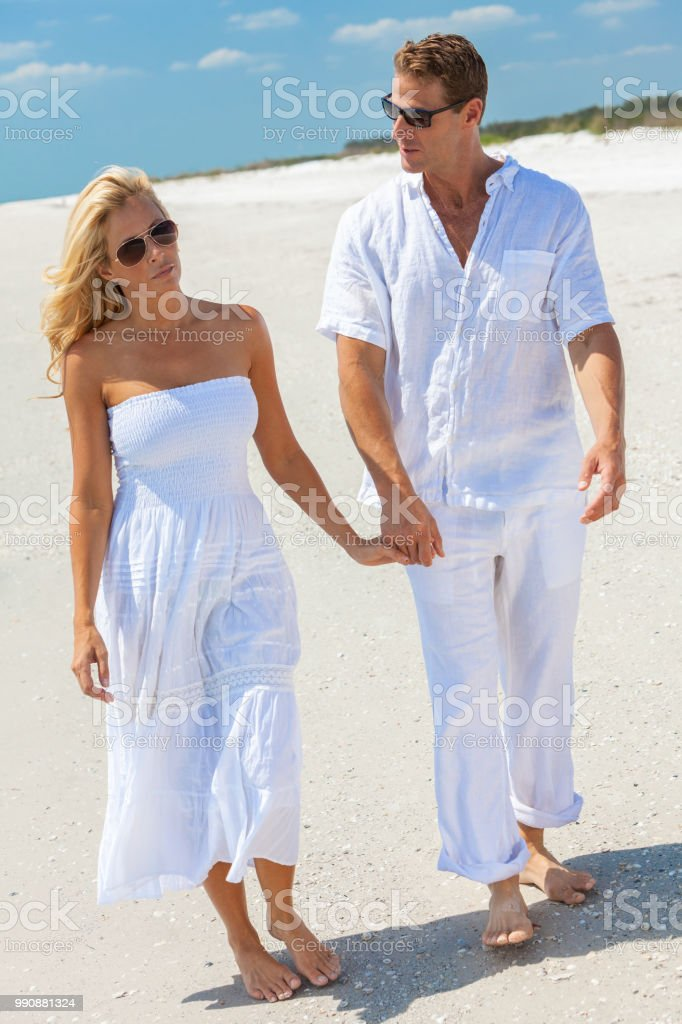 0f8a4f739ebb Sad thoughtful man and woman romantic couple in white clothes holding hands  walking on a deserted tropical beach - Stock image .