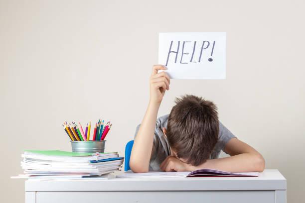 traurig müde frustrierten jungen, die mit vielen büchern am tisch sitzen und papier mit wort hilfe halten. lernschwierigkeiten, bildungskonzept. - frustration stock-fotos und bilder