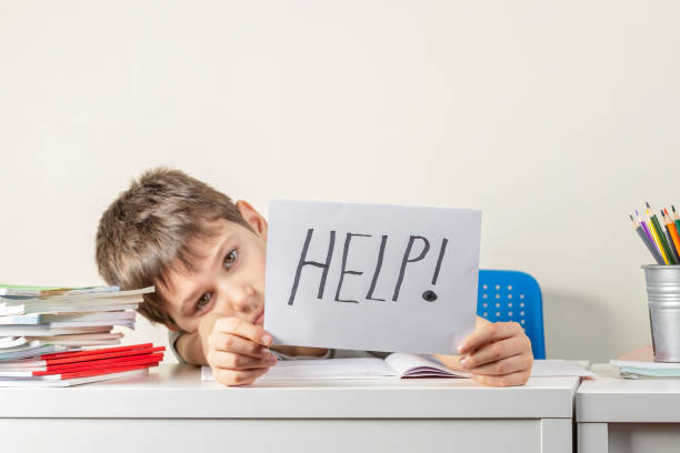 Trauriger, frustrierter Junge, der mit vielen Büchern am Tisch sitzt und Papier mit Wort Hilfe hält. Lernschwierigkeiten, Bildungskonzept. – Foto