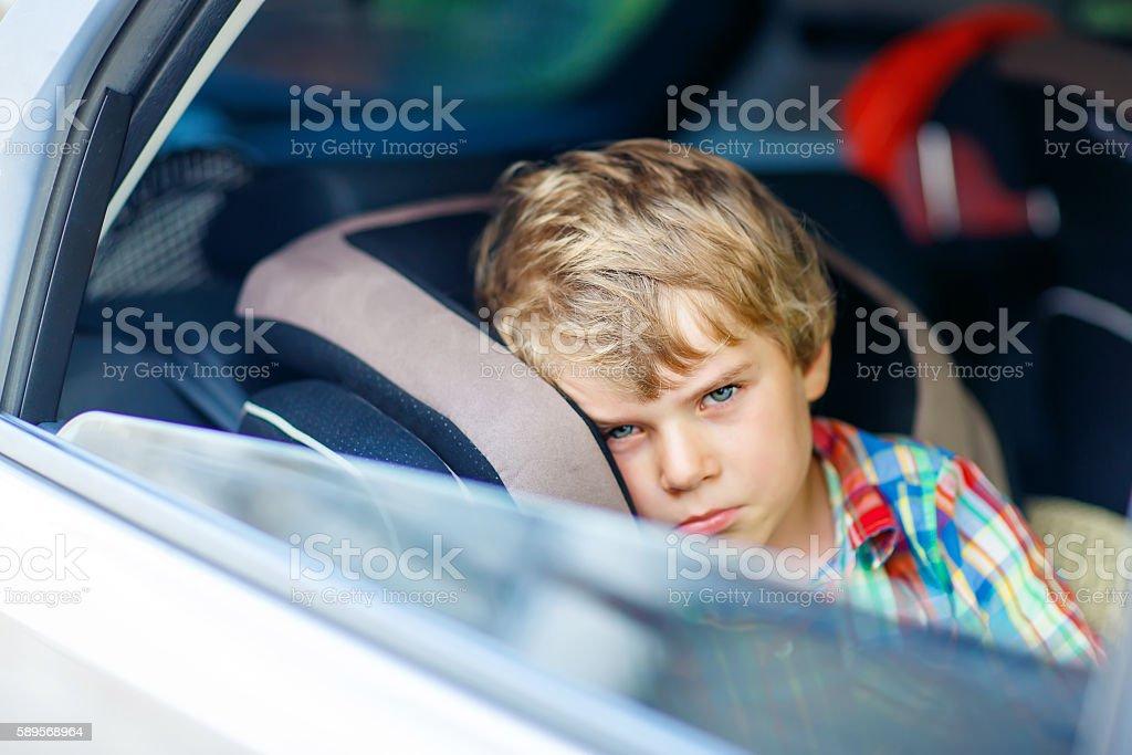 Sad tired kid boy sitting in car  during traffic jam - Foto de stock de Actividad libre de derechos