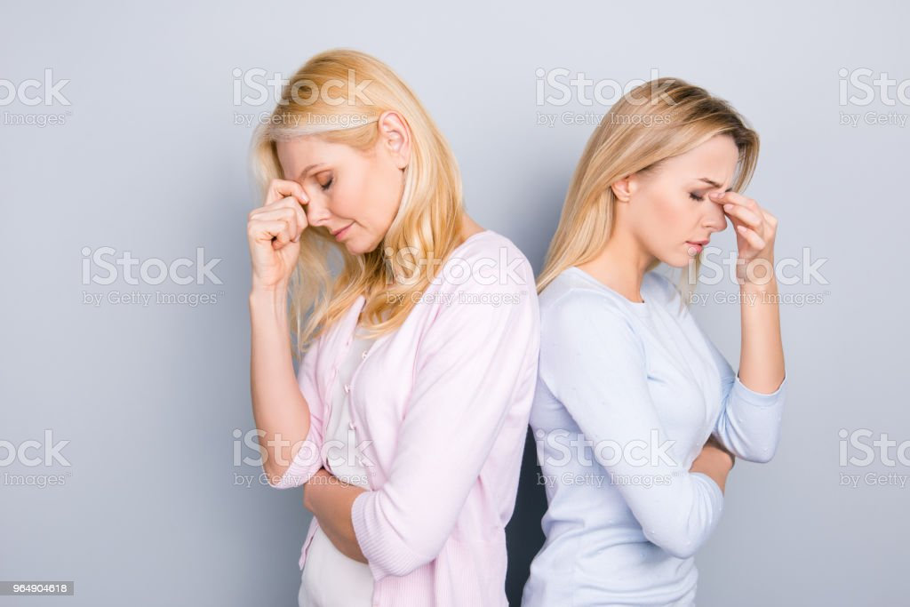 Sad tired unhappy disappointed parent and adult child standing back to back holding fingers hands between eyes on nose keeping eyes closed having negative emotions isolated on grey background royalty-free stock photo