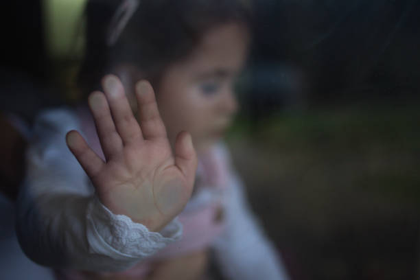 Sad toddler girl Sad and depressed baby girl is leaning her hand on window exploitation stock pictures, royalty-free photos & images