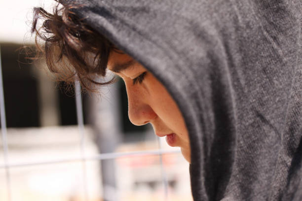 슬픈 고민 스페인 학교 보 십 대는 까마귀 포즈 야외 착용 - 십대 소년 뉴스 사진 이미지