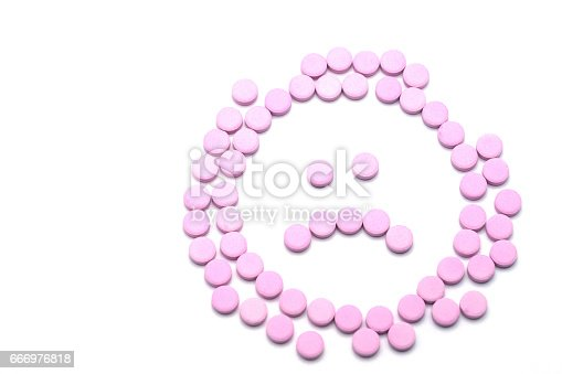 istock Sad unhappy face of pink pills  on white background. Tablets of drug for asthma treatment 666976818