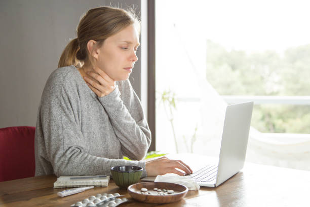 Sad unhappy freelancer working despite sore throat Sad unhappy freelancer working despite sore throat. Young woman sitting at desk with laptop, pills, thermometer and holding neck. Catching cold concept despite stock pictures, royalty-free photos & images