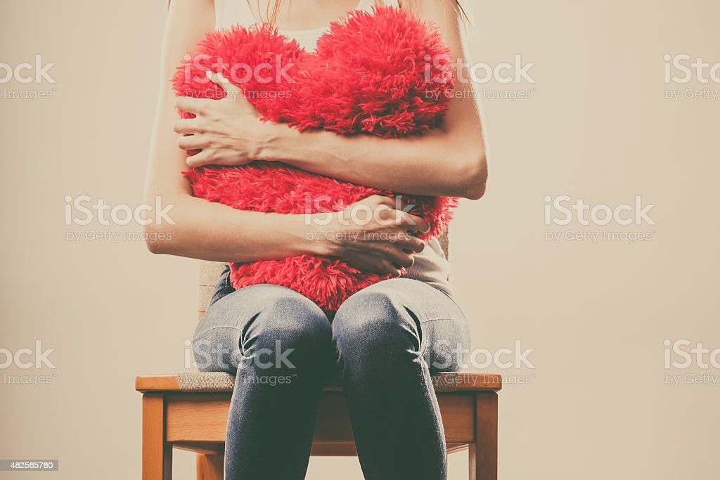 Sad unhappy woman holding red heart pillow bildbanksfoto