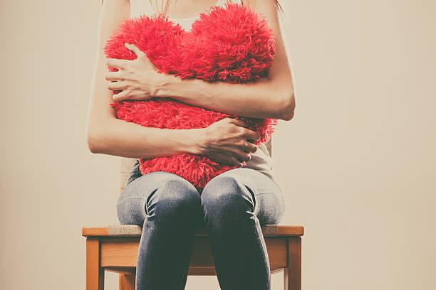 sad unhappy woman holding red heart pillow - liefdesverdriet stockfoto's en -beelden