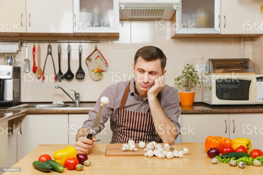Sad upset caucasian young man in apron, brown shirt sitting at table with vegetable, cutting champignon mushrooms in light kitchen. Dieting concept. Healthy lifestyle. Cooking at home. Prepare food. stock photo