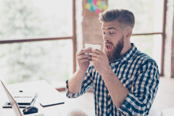 Sad upset ill handsome attractive coughing with high temperature closed eyes  manager business businessman freelancer feeling discomfort using paper tissue checkered casual shirt light modern office stock photo