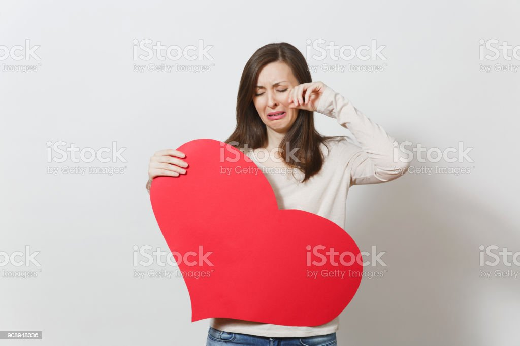 Sad upset lamentable weeping crying woman holding big red heart in hands on white background. Copy space for advertisement. Place for text. St. Valentine's Day or International Women's Day concept. stock photo