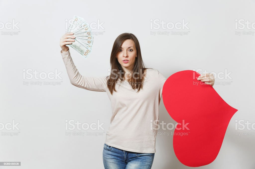 Sad upset lamentable woman holding big red heart, bundle of cash money dollars on white background. Copy space for advertisement. Place for text. St. Valentine's Day, International Women's Day concept stock photo