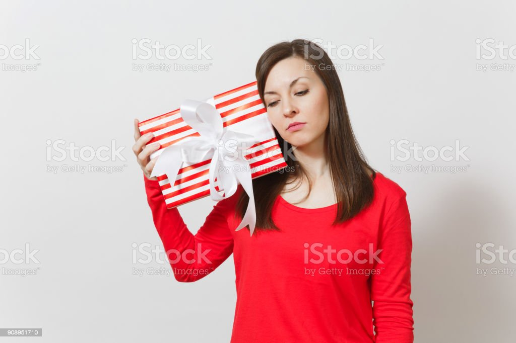 Sad upset woman holding red striped present box with ribbon, bow isolated on white background. For advertisement. St. Valentine's Day, International Women's Day, Christmas, birthday, holiday concept. stock photo