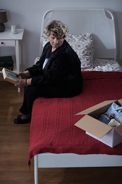 Sad widow sitting on bed stock photo