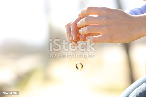 istock Sad wife hands dropping her wedding ring 504370842