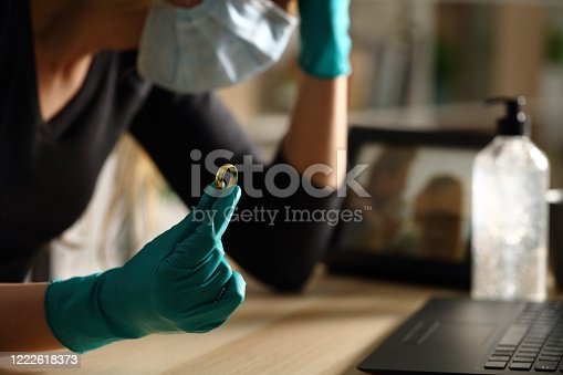 istock Sad wife holding wedding ring on coronavirus confinement 1222618373