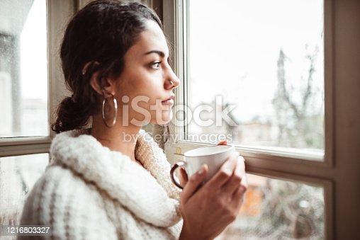 917874758 istock photo sad woman at home for the corona virus 1216803327