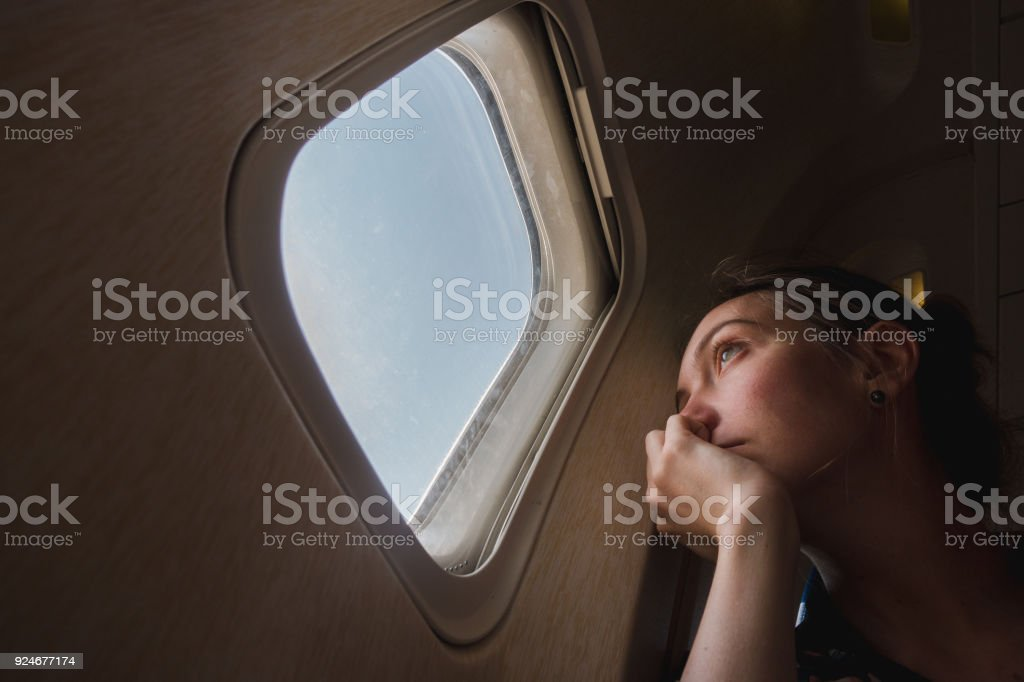 Sad woman at porthole in plane stock photo