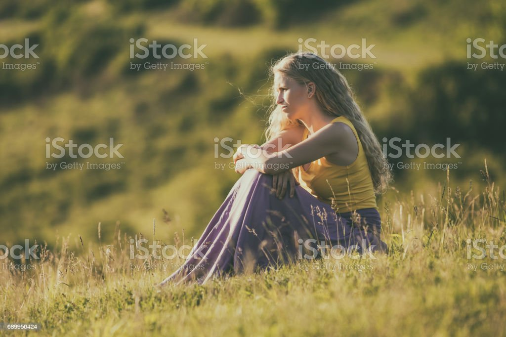 Sad woman at the meadow stock photo