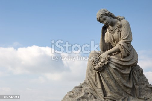 Sad mourning woman with cloud background; a cemetery statue against blue sky.