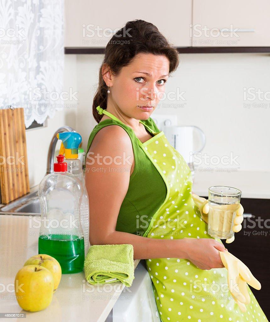 Sad woman cleaning furniture stock photo