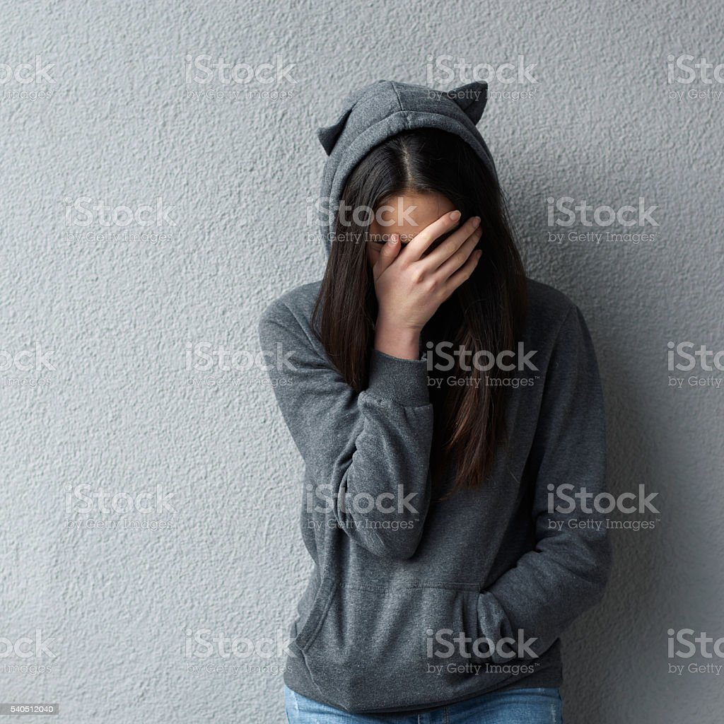 Sad woman covering face with hand stock photo