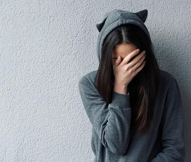 traurige frau mit hand auf gesicht - camouflagekleidung mädchen stock-fotos und bilder