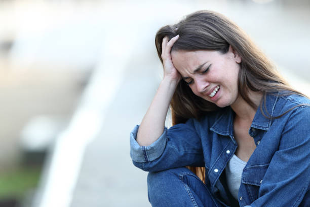 Sad woman crying in the street stock photo