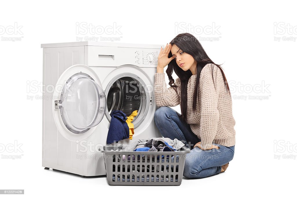 Sad woman emptying a washing machine stock photo