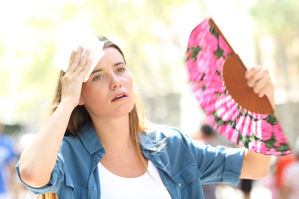 Sad woman fanning and sweating suffering a heat stroke stock photo