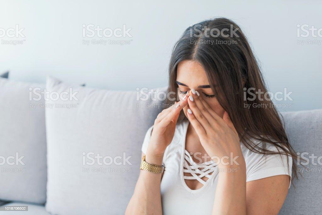 Triste mujer le la nariz y la cabeza debido a dolor de seno - foto de stock