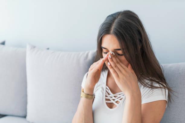 treurige vrouw met haar neus en hoofd omdat sinus pijn - bijholte stockfoto's en -beelden