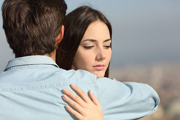 Sad woman hugging her boyfriend couple problems stock photo