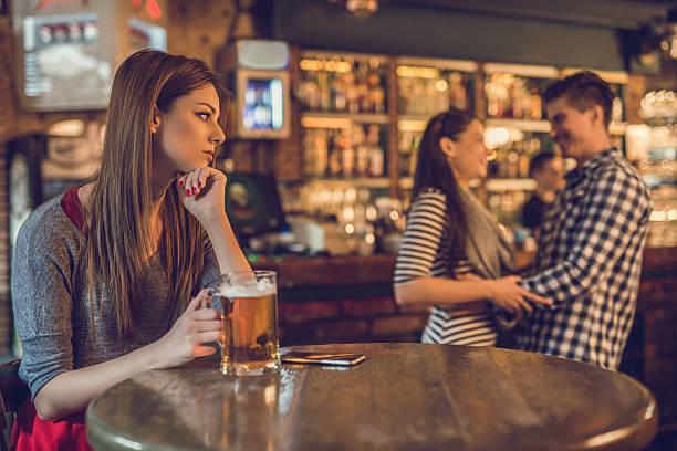 悲しげな女性バーでお求めのカップルのバックグラウンド。 - 羨望 ストックフォトと画像