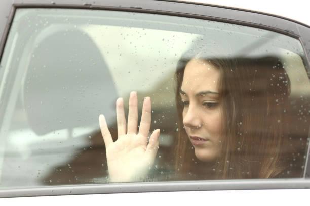traurige frau in einem auto bei einem roadtrip - trauer abschied tod stock-fotos und bilder