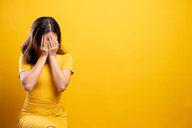 Sad woman isolated over yellow background stock photo