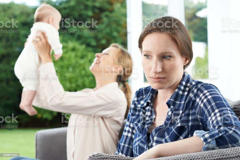 Sad Woman Jealous Of Friend With Young Baby stock photo